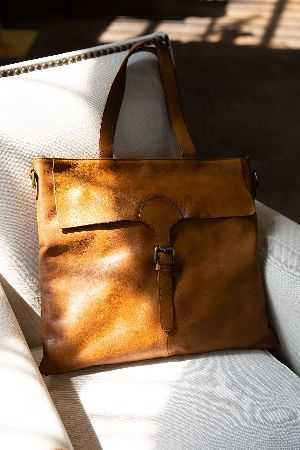 Vintage colored leather satchel featureing metal buckel